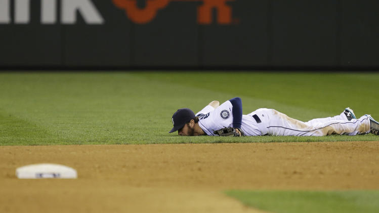 Seattle Mariners second baseman Nick Franklin lies on at the grass after he deflected a single hit by Boston Red Sox's David Ortiz in the eighth inning of a baseball game, Tuesday, July 9, 2013, in Seattle. (AP Photo/Ted S. Warren)
