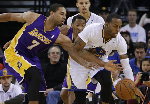 Los Angeles Lakers' Xavier Henry, left, fights for the ball with Golden State Warriors' Andre Iguodala (9) during the first half of an NBA basketball game Saturday, Dec. 21, 2013, in Oakland,