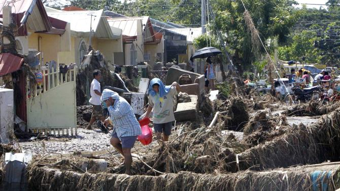 Residents return to their homes to save some household items Sunday, Dec. 18, 2011 at Iligan city in southern Philippines. Tropical storm Washi blew away Sunday after devastating the southern Philippines with flash floods that killed hundreds of people as they slept and turned two coastal cities into a muddy wasteland filled with overturned cars and uprooted trees. (AP Photo/Bullit Marquez)