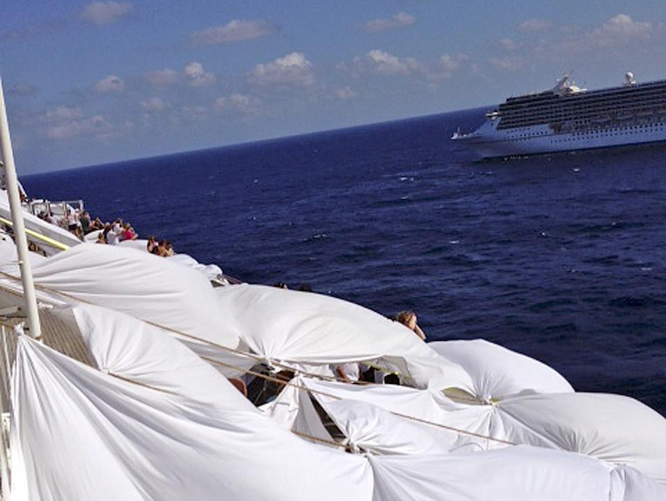This Sunday, Feb. 10, 2013 photo, provided by Kalin Hill, of Houston, shows passengers with makeshift tents on the the deck of the Carnival Triumph cruise ship at sea in the Gulf of Mexico. The ship nearing Mobile Bay is without engine power and is being towed by tugboats. (AP Photo/Kalin Hill)