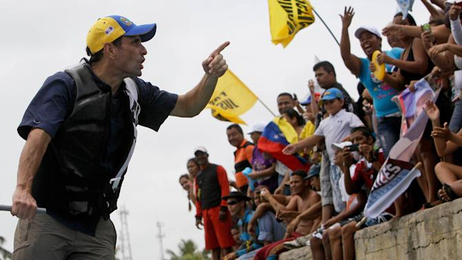 Opposition presidential candidate Henrique Capriles greets supporters during a campaign visit at Morrocoy Keys near Chichiriviche, Venezuela, on Good Friday, March 29, 2013. Holy Week in Venezuela is a time when millions traditionally take a welcome pause from work and politics to go on vacation. Yet that hasn't stopped Venezuela's time-pressed presidential candidates from sprinting through the holidays toward an April 14 election to replace the late Hugo Chavez, as they try to define both themselves and each other within weeks. Capriles will run against Chavez's chosen successor, acting President Nicolas Maduro.(AP Photo/Fernando Llano)