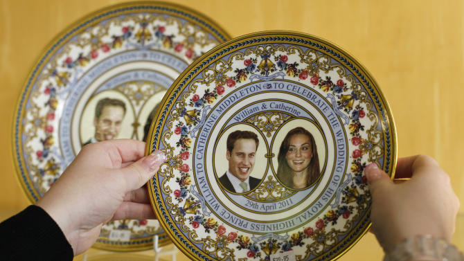 In this Wednesday, March 9, 2011 photo, a member of staff adjusts a commemorative plate for the Royal Wedding of Prince William and Kate Middleton at Church's china shop in Northampton, England. Surrounded by a mountain of boxes in a rickety old warehouse above the family shop, Joe Church is hard pressed to keep up the pace as he wraps a plate adorned with the faces of Prince William and his bride Kate Middleton for a customer in Australia. Church's, a 152-year old china and ornament seller that specialises in memorabilia, has plenty of reason to celebrate the upcoming royal nuptials as its cash register chimes with the wedding bells. (AP Photo/Alastair Grant)