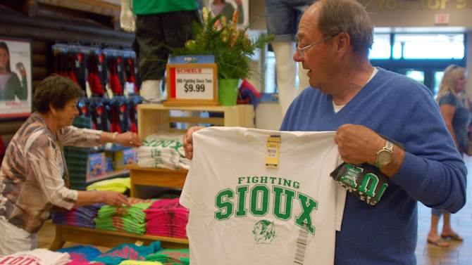 Buck Striebel holds up a University of North Dakota Fighting Sioux T-shirt while his wife, GaeLynn, sorts through other shirts on sale at a sporting goods store in Bismarck, N.D., Tuesday, June 12, 2012. Buck Striebel, a graduate of North Dakota State University, said he would vote to keep the nickname of the rival school. GaeLynn, and the couple's son, Robert, are UND graduates and said they would vote to get rid of the controversial nickname. (AP Photo/James MacPherson)