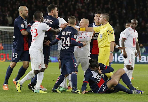 Paris-Saint-Germain's and Lille's players argue with referee Fredy Gautrel, second from right, while Lille's Antonio Mavuba, right, looks at Zlatan Ibrahimovic of Sweden as he lies on the