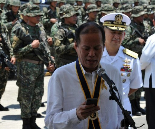 "Philippine President Benigno Aquino looks at his mobile phone after the navy's anniversary celebration at Fort San Felipe, on May 21, 2013. Aquino has announced a $1.8-billion military upgrade to help defend his country's maritime territory against ""bullies"", amid an ever-worsening dispute with China."