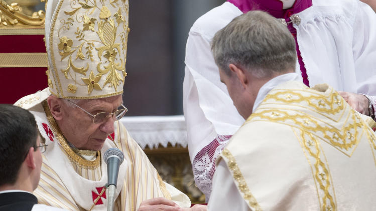 Pope Benedict XVI offers his personal secretary Georg Ganswein the ring as he names him bishop during an Epiphany mass in St.Peter's Basilica at the Vatican, Sunday, Jan. 6, 2013. The Epiphany day, is a joyous day for Catholics in which they recall the journey of the Three Kings or Magi to pay homage to Baby Jesus. (AP Photo/Andrew Medichini)