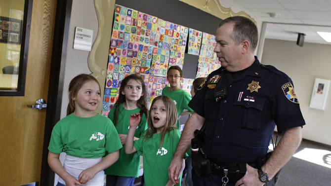FILE - In this Thursday, Jan. 31, 2013 file photo, Douglas County Sheriff Department Lt. Brian Murphy is greeted by children at Buffalo Ridge Elementary School, part of a new cooperative effort between law enforcement and schools for more routine police presence at local primary schools, in Castle Pines, Colo. Since the December school attack in Connecticut, county police have begun a practice of completing their paperwork from their cruisers in elementary school parking lots, and are encouraged to spend more time inside schools. (AP Photo/Brennan Linsley, File)