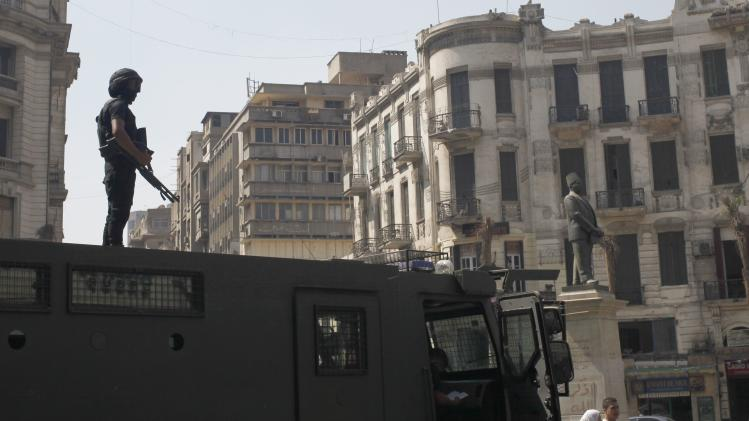 A policeman stands guard over a police vehicle in central Cairo ahead of expected protests