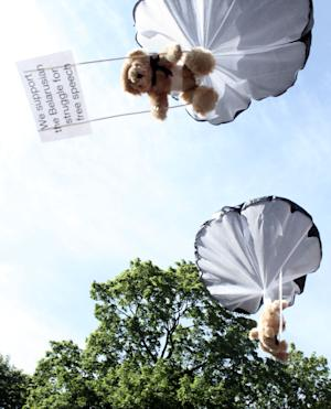 In this undated photo provided by Studio Total teddy bears hang on parachutes during a training in Stockholm, Sweden. Thomas Mazetti and Hannah Frey from Sweden intruded with a light plane on the Belarus' airspace and dropped hundreds of teddy bears carrying slogans supporting human rights and media freedom, on July 4, 2012. The two Swedes behind the stunt, said their idea was to show support for Belarusian human rights activists and to embarrass the country's military, which is a pillar of President Lukashenko's power. (AP Photo/Studio Total/Per Cromwell)