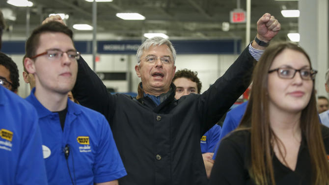 Best Buy CEO Hubert Joly, center, reacts to the store manager who speaks to employees before the store opens on Thanksgiving, Thursday, Nov. 26, 2015, in Minnetonka, Minn. (AP Photo/Bruce Kluckhohn)
