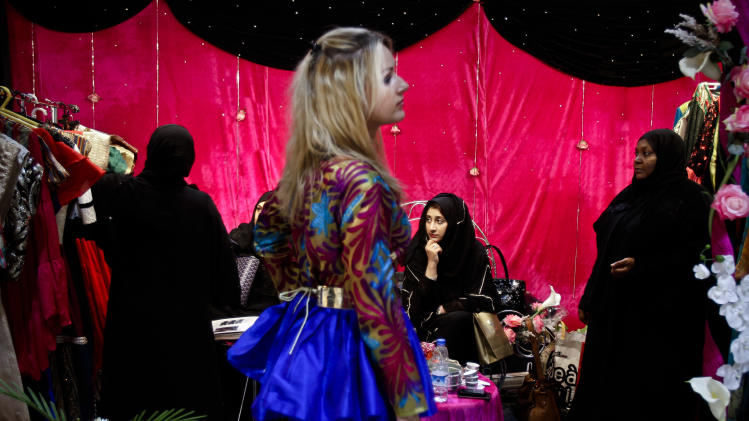 In this Saturday, April 13, 2013 photo, a Russian model, middle, tries to attract visitors, as Bahraini Fashion Designer Iman Al Seyed, 1st left, presents her collection to customers at her designer's stand at a bridal exhibition, Dubai, United Arab Emirates. Just a few years ago, Gulf Arab women usually only felt comfortable showing off their fashion sense at ladies-only parties or family gatherings. In public, at least in their home countries, the standard all-black abaya _ a simple floor-length covering and accompanying head scarf _ was the only culturally accepted option. But now a new generation of abaya designers are giving the traditional garment a twist with choices of fabric, designs and even some expensive bling to allow Gulf women a host of style options.  (AP Photo/Kamran Jebreili)