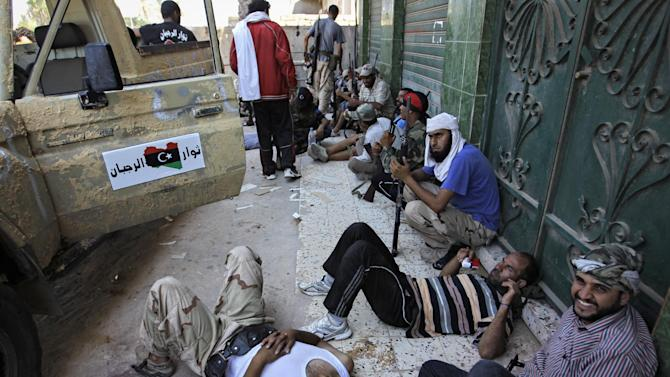 Rebel fighters rest in the shade in the village of Mayah, some 30 kilometers west from Tripoli, Libya, Sunday, Aug. 21, 2011.  Libyan rebels said they were less than 20 miles (30 kilometers) from Moammar Gadhafi's main stronghold of Tripoli on Sunday, a day after opposition fighters launched their first attack on the capital itself. Fighters said a 600-strong rebel force that set out from Zawiya has reached the outskirts of the village of Jedaim and was coming under heavy fire from regime forces on the eastern side of the town. (AP Photo/Sergey Ponomarev)