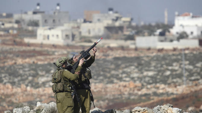 Israeli soldiers fire tear gas during clashes with Palestinian protesters, not seen, near the west bank village of Qusra, near Nablus, Tuesday, Jan. 1, 2013. In the West Bank Monday, Palestinian President Mahmoud Abbas said he would agree to resume negotiations with Israel under the auspices of an international peace conference. (AP Photo/Nasser Ishtayeh)
