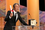 Danish actor Mads Mikkelsen celebrates on stage after being awarded with the Prix d'Interpretation Masculine (Best Actor) during the closing ceremony of the 65th Cannes film festival in Cannes