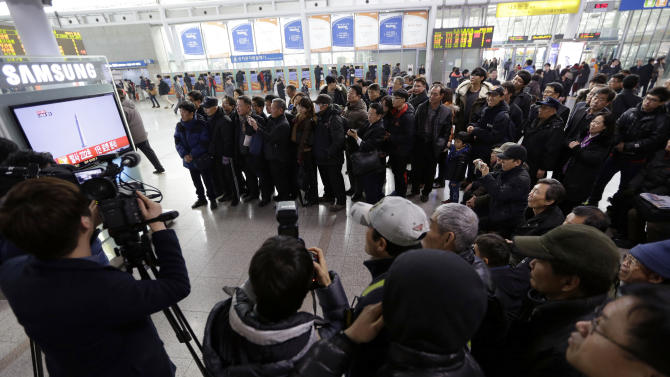 People watch a public TV reporting the country's rocket launch, at Seoul Railway Station in Seoul, South Korea, Wednesday, Jan. 30, 2013. South Korea says it has successfully launched a satellite into orbit from its own soil for the first time. Wednesday's high-stakes launch comes just weeks after archrival North Korea successfully launched its own satellite to the surprise of the world. (AP Photo/Lee Jin-man)
