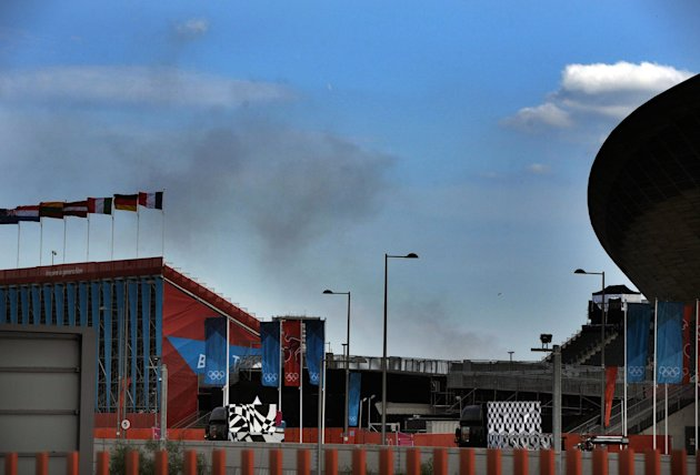 Smoke rises from a fire at a recycling center on Chequers Lane in Dagenham, east London, behind the Olympic Park's BMX track on Sunday, Aug. 12, 2012.(AP Photo/Anthony Devlin, PA) UNITED KINGDOM OUT; NO SALES; NO ARCHIVE