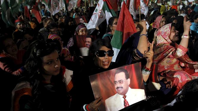 A supporter of Pakistan's Muttahida Qaumi Movement (MQM) political party holds a poster of MQM chief Altaf Hussain while chanting slogans during a by-election campaign rally in Karachi