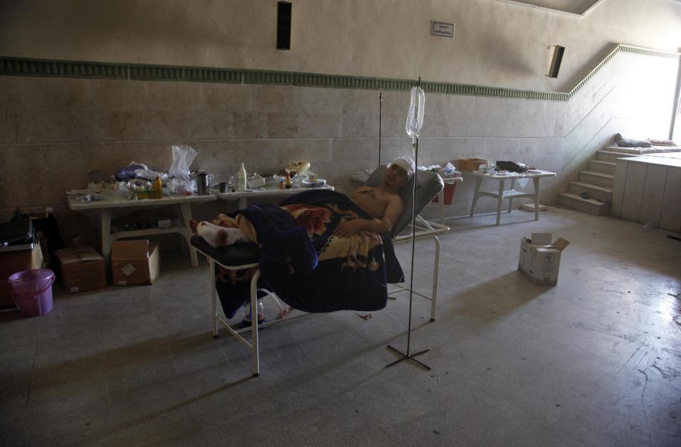 Palestinian refugee, Mohammed, first name not given, rests in a field hospital after he was found in an open area with three gunshot wounds among the bodies of nine other people  in the town of Anadan on the outskirts of Aleppo, Syria, Monday, Aug. 6, 2012. (AP Photo)