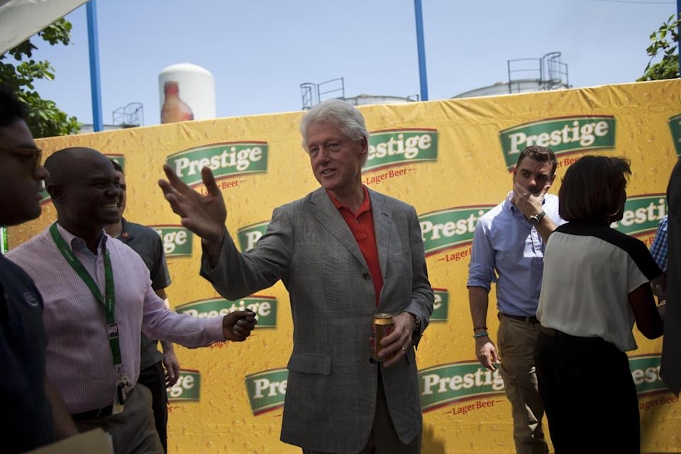 Former U.S. President and UN special envoy to Haiti, Bill Clinton speaks while he holds a beer during a visit to the Heineken/Brana Brewery S.A. in Port-au-Prince, Haiti. Monday March. 11, 2013. (AP Photo/Dieu Nalio Chery)