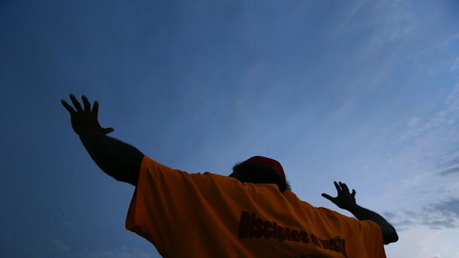"""Jerry """"Uncle Black"""" Rodgers, a Ferguson resident, raises his hands during a protest on West Florissant Avenue in Ferguson, Mo. on Wednesday, Aug. 20, 2014. On Aug. 9, 2014, a white police officer fatally shot Michael Brown, an unarmed black 18-year old, in the St. Louis suburb. (AP Photo/Atlanta Journal-Constitution, Curtis Compton)"""