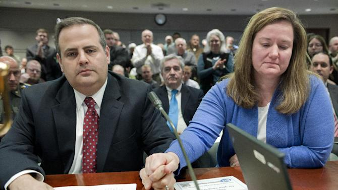 Mark and Cindy Mattioli hold hands as they receive a standing ovation after testifying at the Legislative Office Building in Hartford, Conn., Monday, Jan. 28, 2013. Mark Mattioli whose 6-year-old son James was killed at Sandy Hook, said there are more than enough gun laws on the books, but they are not being properly enforced. (AP Photo/Jessica Hill)