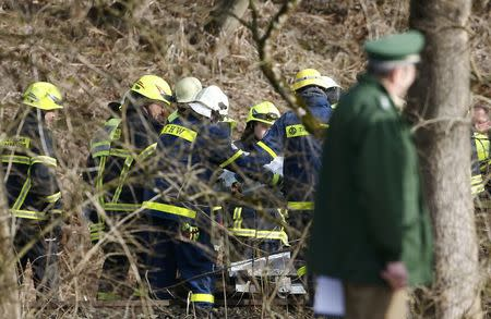 Members of emergency services carry a body bag at the site of the two crashed trains near Bad Aibling