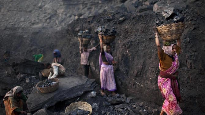 FILE - In this Jan. 7, 2011 file photo, people carry baskets of coal scavenged illegally at an open-cast mine in the village of Bokapahari in the eastern Indian state of Jharkhand where a community of coal scavengers live and work. India's Parliament is in an uproar over a report by government auditors that the country lost nearly US$210 billion in revenue by selling off coalfields to private and state-run companies without competitive bidding. (AP Photo/Kevin Frayer, File)