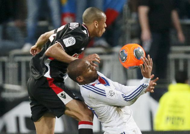 Olympique Lyon's Briand challenges Henrique of Monaco during their French Ligue 1 soccer match at the Gerland stadium