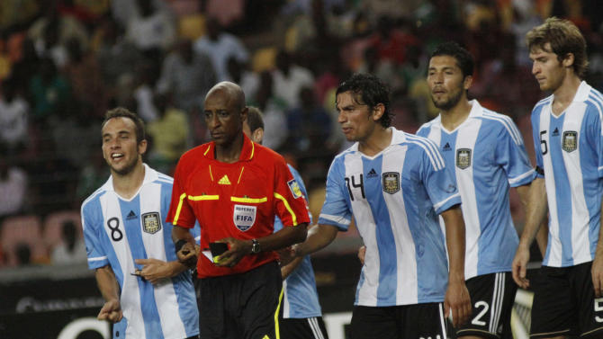 FILE -  In this Wednesday, June 1, 2011 file photo,  referee Ibrahim Chaibou, red top,  is surrounded by Argentina soccer players after he awarded a penalty against them during an international friendly soccer match with Nigeria Super eagles at the National stadium in  Abuja, Nigeria. It was in the final minutes of the June 2011 soccer game between Nigeria and Argentina when the little green flags on computer screens in London started to change color. Nigeria was leading 4-0 in the exhibition match of little significance, and more and more money was being laid down on the possibility that one of the teams would score another goal before the game was over. Monitors hired by soccer's governing body FIFA to detect deviations from expected betting patterns _ helped by computer algorithms _ spotted something fishy. The game's 90 minutes of regular time ended without another goal. Referee Ibrahim Chaibou ordered extra time added to the clock _ normal in most soccer games to make up for stoppages in play throughout the contest for injuries or other minor delays. He added six minutes _ a substantial amount for such a minor game. (AP Photo/Sunday Alamba, file)