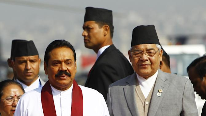 Sri Lankan President Mahinda Rajapaksa, left in white, poses with Nepalese Home Minister Bam Dev Gautam, as he arrives at the Tribhuwan Airport to attend the 18th summit of South Asian Association for Regional Cooperation (SAARC) in Katmandu, Nepal, Tuesday, Nov. 25, 2014. Leaders from Afghanistan, Bangladesh, Bhutan, India, Maldives, Nepal, Pakistan and Sri Lanka will meet as a group and also hold bilateral discussions on the sidelines of the summit on Wednesday and Thursday. (AP Photo/Niranjan Shrestha)