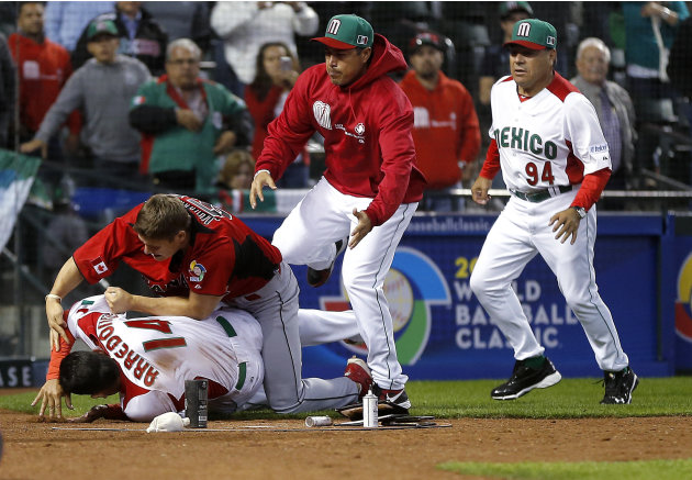 Canada's Jay Johnson, top left, and Mexico's Eduardo Arredondo fight during the ninth inning of a World Baseball Classic game, Saturday, March 9, 2013, in Phoenix. (AP Photo/Matt York)
