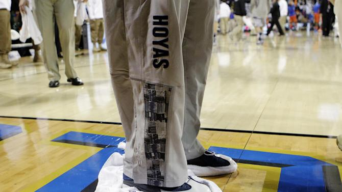 A Georgetown player wipes the court with a towel trying to dry condensation before the start of the second half of the Navy-Marine Corps Classic NCAA college basketball game against Florida aboard the USS Bataan at the Mayport Naval Station, Friday, Nov. 9, 2012, in Jacksonville, Fla. The game was called because the floor could not be dried. (AP Photo/John Raoux)