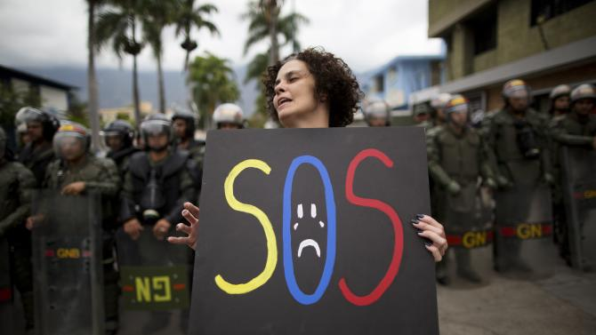 A demonstrator holds a homemade poster in front of a cordon of National Bolivarian National Guard during a protest near the Cuban embassy in Caracas, Venezuela, Tuesday, Feb. 25, 2014. Opponents of President Nicolas Maduro marched to the Cuban Embassy to protest what they consider the communist nation's interference in Venezuela's internal affairs. (AP Photo/Rodrigo Abd)