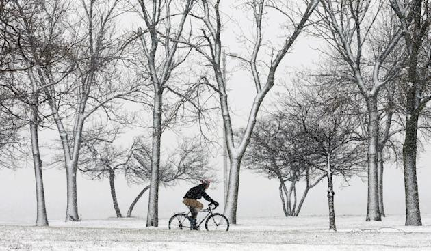 A lone cyclist navigates the bike path through a snow storm at Chicago's North Ave. beach Thursday, Dec. 27, 2012. A muted version of the deadly winter storm that has killed more than a dozen across t