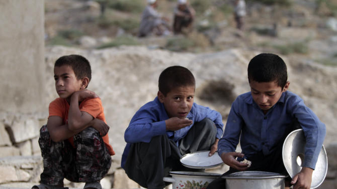 Afghans children eat free food donated by other villagers as they break their fast during the second week in the holy month of Ramadan in Kabul, Afghanistan, Wednesday, July 17, 2013. Ramadan is the holiest month in Islam and observant Muslims worldwide observe it by fasting from dawn to dusk. (AP Photo/Rahmat Gul)