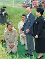 FILE - In this May 14, 1996 file photo, Thailand's King Bhumibol Adulyade, standing left, and Queen Sirikit survey the rice crop made possible by a Royal Irrigation Project which uses floodwaters to irrigate a second harvest of rice during the dry season in Ayuthaya, 70 kilometers (44 miles) north of Bangkok. Water has been a virtual obsession for the king for the past four decades. The 83-year-old monarch has warned about the dangers of overdevelopment and developed ideas to mitigate the damage from floods. (AP Photo/Charles Dharapak,File)