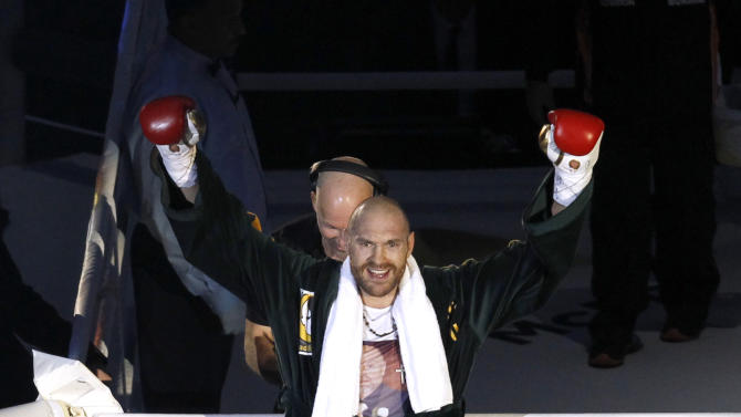 Tyson Fury gestures to fans as he enters the ring before the start of the fight