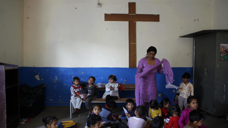In this Wednesday, Oct. 17, 2012, photo, Pakistani teacher Dolores Arif, 40, teaches the alphabet to children in a church in a Christian neighborhood in Islamabad, Pakistan. A teenage activist recently shot and critically wounded by the Taliban risked her life to attend school, but the threat from the militant group is just one of many obstacles Pakistani girls face in getting an education. Others include rampant poverty, harassment and the government's failure to prioritize education spending. (AP Photo/Nathalie Bardou)