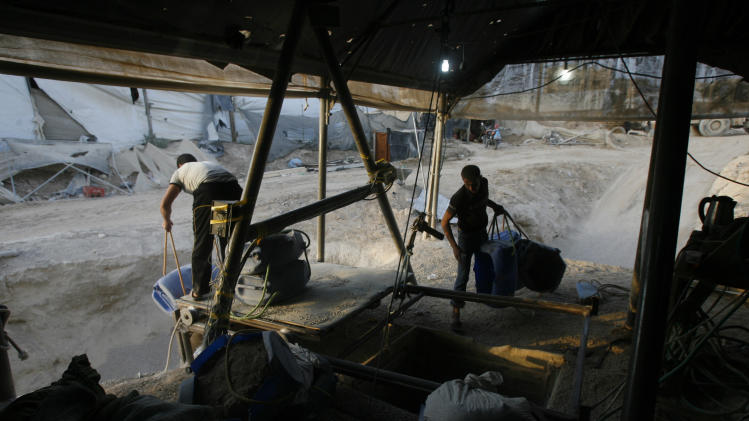 In this Saturday, May 28, 2011 file photo, Palestinians smuggle goods used for construction through a tunnel from Egypt to the Gaza Strip in Rafah, southern Gaza Strip. Hamas had hoped the Islamists who took charge in Egypt  this summer -- fellow members of the region's Muslim Brotherhood -- would swiftly turn their shared border crossing into a free-flowing trade route, ending Gaza's five-year isolation from the world and making the tunnels obsolete. (AP Photo /Eyad Baba, File)