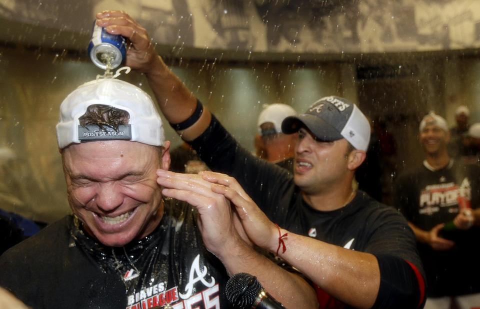 Atlanta Braves' Chipper Jones, left, is doused with beer by teammate Martin Prado after the Braves beat the Miami Marlins 4-3 in a baseball game to clinch at least an NL wild-card berth, Tuesday, Sept. 25, 2012, in Atlanta. (AP Photo/David Goldman, Pool)