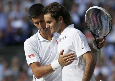 Novak Djokovic of Serbia speaks with Roger Federer of Switzerland after defeating him in their men's singles finals tennis match on Centre Court at the Wimbledon Tennis Championships in London