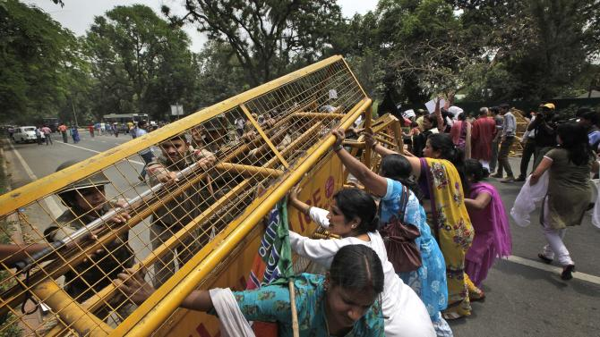 Indian women activists of India main opposition Bharatiya Janata Party remove police barricade outside ruling United Progressive Alliance chairperson Sonia Gandhi's residence during a protest against the rape of a 5-year-old girl in New Delhi, India, Sunday, April 21, 2013. The girl was raped and tortured by a man who held her in a locked room in India's capital for two days. (AP Photo/Manish Swarup)