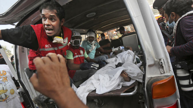 A Bangladeshi garment worker who was pulled alive from the rubble lays in the back of an ambulance after being brought by rescue workers at the site of a building that collapsed Wednesday in Savar, near Dhaka, Bangladesh, Friday, April 26, 2013. The death toll reached hundreds of people as rescuers continued to search for injured and missing, after a huge section of an eight-story building that housed several garment factories splintered into a pile of concrete.(AP Photo/Kevin Frayer)