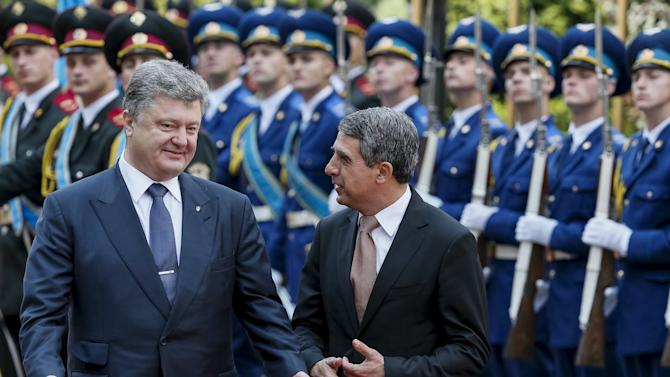 Ukraine's President Poroshenko and his Bulgarian counterpart Plevneliev chat as they inspect an honour guard during a welcoming ceremony in Kiev