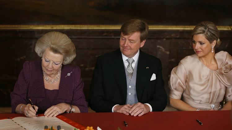 Dutch Queen Beatrix, left signs the Act of Abdication in favour of her son, Prince Willem-Alexander, centre and Princess Maxima, right, in the Mozeszaal or Mozes hall of the Royal Palace in Amsterdam, The Netherlands, Tuesday April 30, 2013. Around a million people are expected to descend on the Dutch capital for a huge street party to celebrate the first new Dutch monarch in 33 years. (AP Photo/Bart Maat, pool)