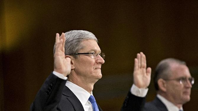 Apple CEO Tim Cook, left, and Phillip A. Bullock, right, Apple's head of Tax Operations, are sworn in on Capitol Hill in Washington, Tuesday, May 21, 2013, prior to testifying before the Senate Homeland Security and Governmental Affairs Permanent subcommittee on Investigations hearing to examine the methods employed by multinational corporations to shift profits offshore and how such activities are affected by the Internal Revenue Code. Lawmakers want to hear from Cook how Apple, the world's most valuable company, based in Cupertino, Calif., holds a billion dollars in an Irish subsidiary as a tax strategy, according to a report issued this week by the subcommittee.  (AP Photo/J. Scott Applewhite)