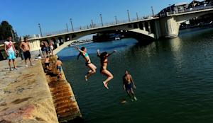 People jump into the Guadalquivir river during a heatwave…