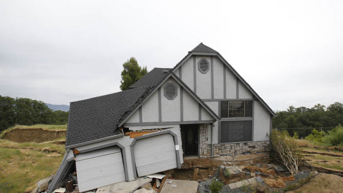 FILE - A Monday, May 6, 2013, file photo shows the wreckage of the Tudor-style dream home Robin and Scott Spivey were forced to abandon after the ground gave way causing it to drop 10 feet below the street in Lakeport, Calif. The homeowners of the sinking Northern California subdivision have filed claims against the county, alleging a leaking county water system is to blame. (AP Photo/Rich Pedroncelli, file)