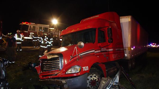 A photo released by the Indiana State Police shows firemen and police examining the wreckage of a fatal accident on the Indiana Toll Road near Bristol, Ind., Thursday Oct. 27, 2011.   A tractor-trailer slammed into the back of a minivan in northern Indiana killing at least seven people and sending four others to hospitals, authorities said.  (AP Photo/Indiana State Police)