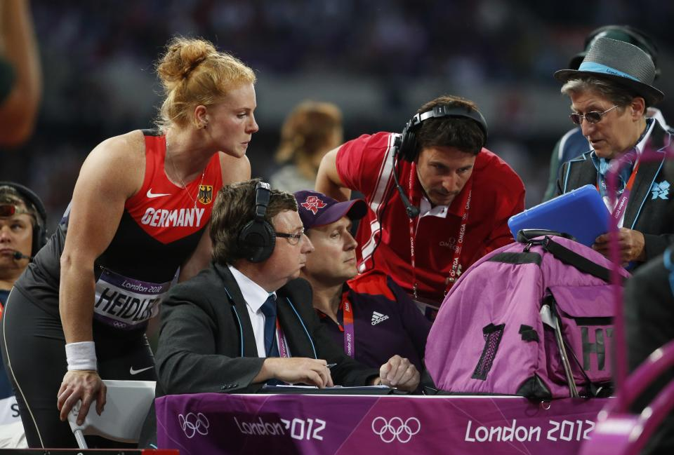 Germany's Betty Heidler, left, looks on as technical judges review her bronze medal winning throw in the women's hammer throw final during the athletics in the Olympic Stadium at the 2012 Summer Olympics, London, Friday, Aug. 10, 2012. (AP Photo/Matt Dunham)